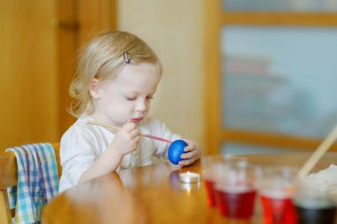 Little girl coloring Easter egg