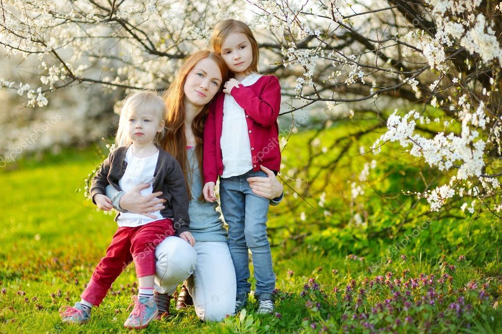 Mother and children in blooming garden