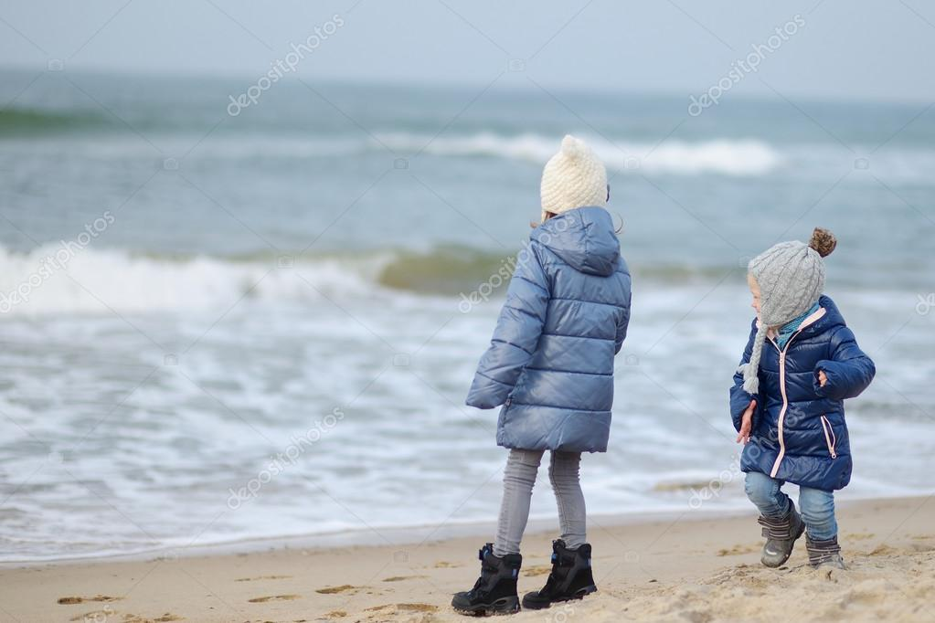 Little sisters near winter ocean