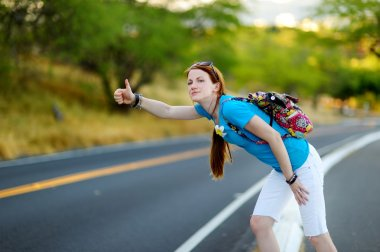 Female tourist hitchhiking on road
