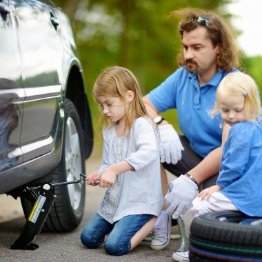 Little girl helping father with car