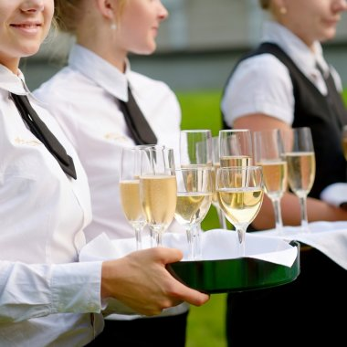 Waitresses with dish of champagne glasses