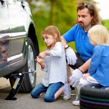 Father and daughters  changing a car wheel