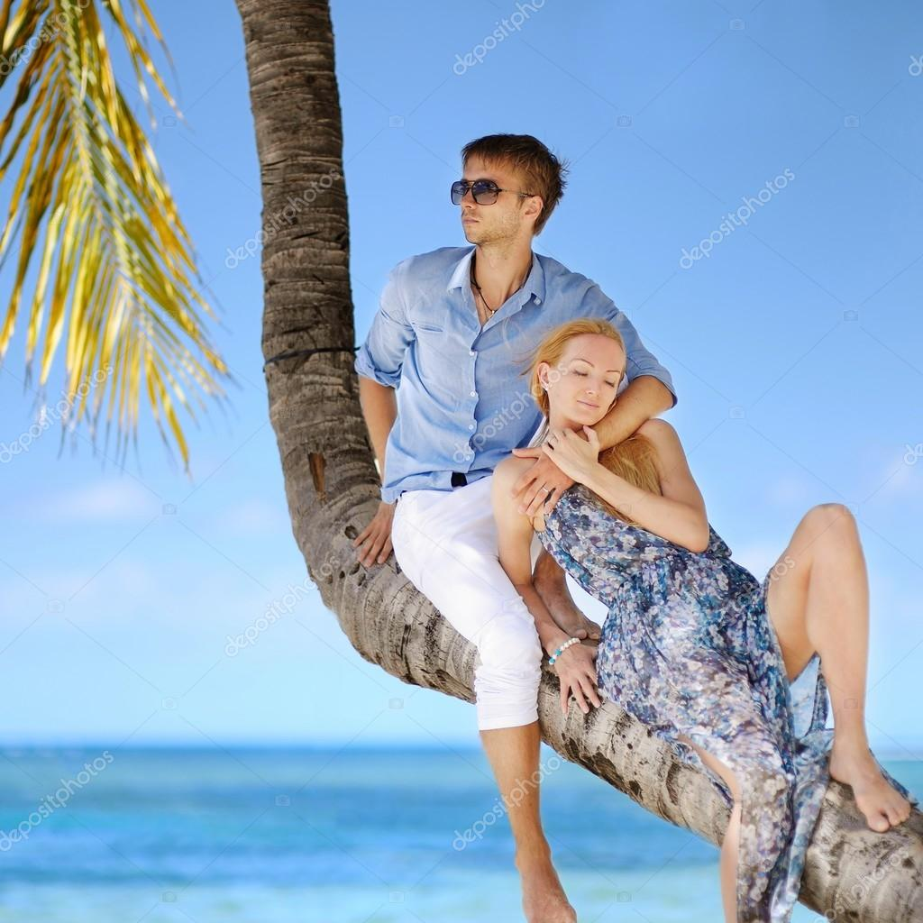 Couple sitting on palm tree