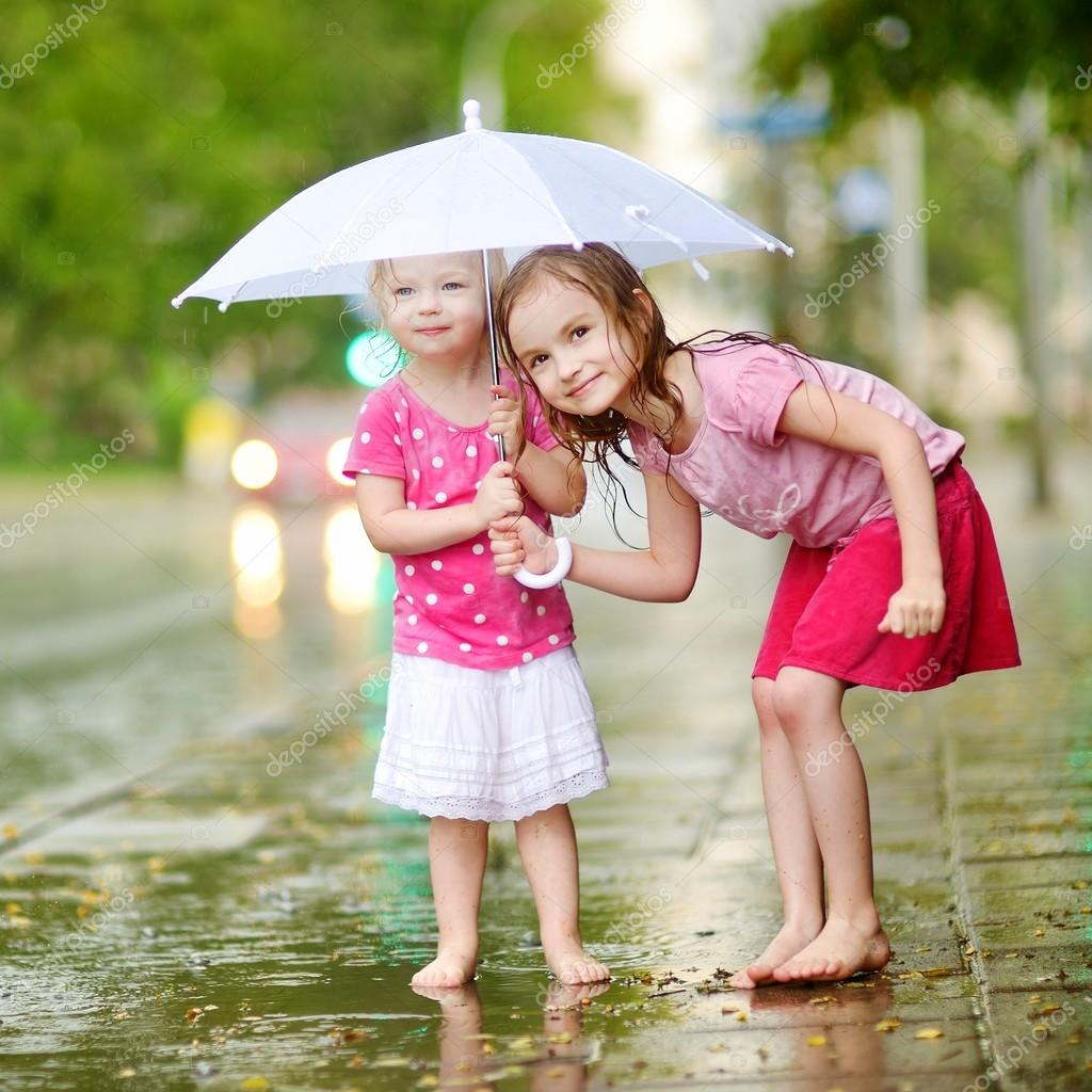 Two cute little sisters with umbrella