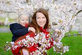 Matka a dítě v rozkvetlé zahradě