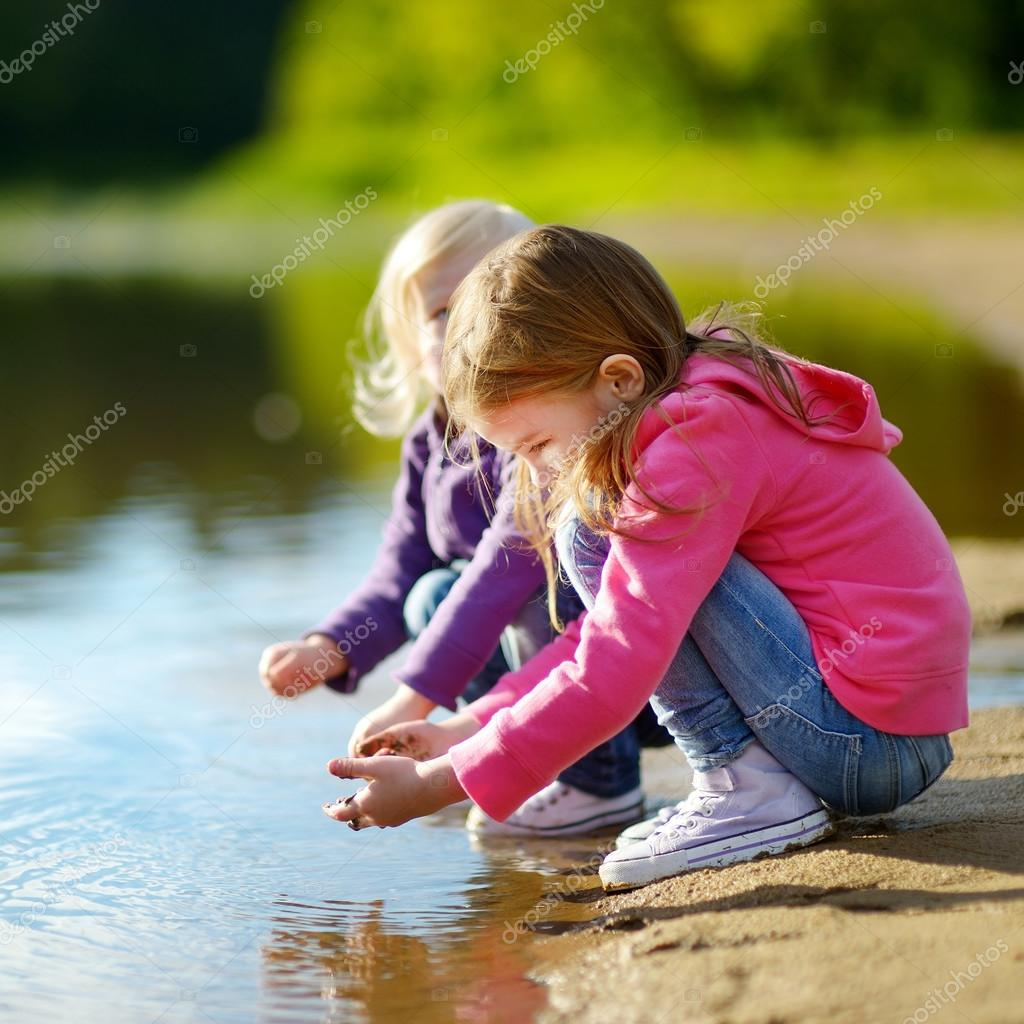 little sisters playing by a river