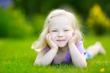 Cute little girl laying in the grass