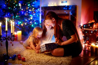 Mother and  daughters opening  Christmas gift