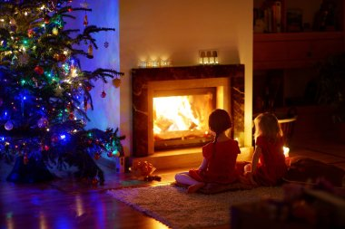 girls sitting by fireplace on Christmas eve