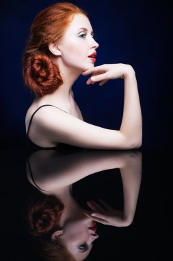 Young woman with ginger hair over reflection mirror on blue back