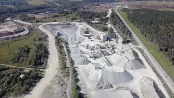 Luftaufnahme des Steinbruchs. Steinbrechmaschine zerkleinert Gestein in Kies. Förderbänder schütten Schotter in hohe Haufen