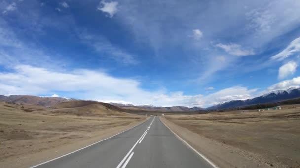 Jízda po horské asfaltové silnici Chuysky Tract podél Kurai Ridge na Altai betveen Aktash a Kuray na jaře. Sibiř, Rusko