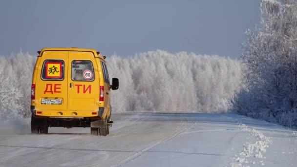 Szibéria, Oroszország - December 18, 2020: Autó havas úton a téli szezonban. Iskolai transzfer busz szállít gyermekek.