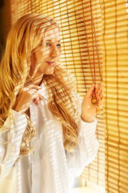 Young happy woman looking out the window through the blinds