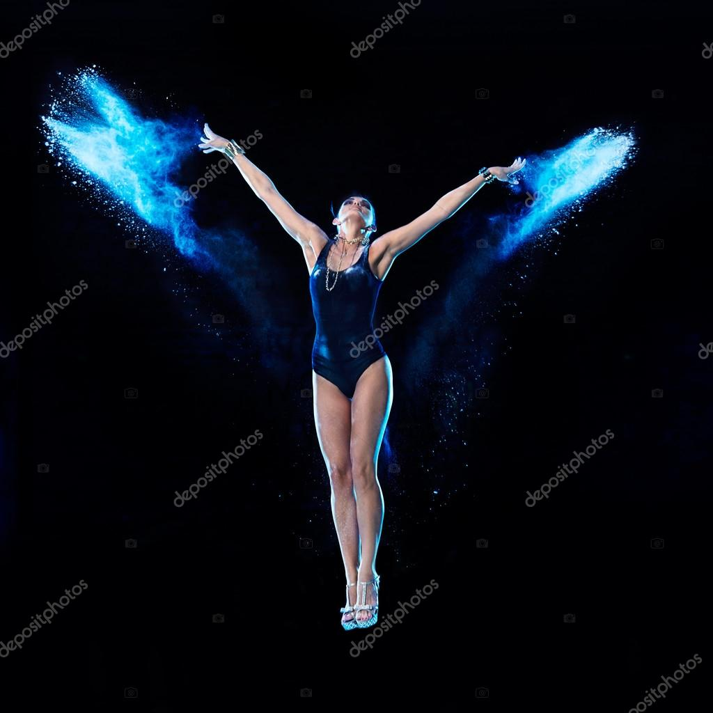 Young woman jumping in blue powder cloud