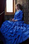 Fiatal nő ül a coupe retro Rai kék vintage ruha