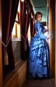 Fiatal nő kék vintage ruha, retro folyosón állandó