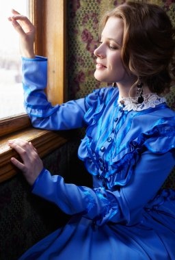 Young woman in blue vintage dress looking out the window in coup