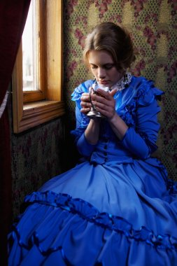 Young woman in blue vintage dress drinking tea in coupe of retro