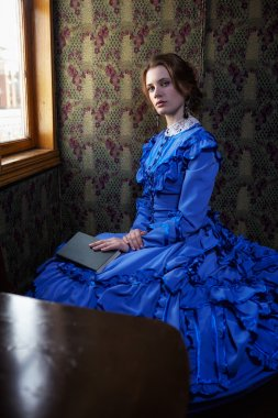 Young woman in blue vintage dress  sitting with book in coupe of