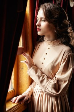 Young woman in beige vintage dress of early 20th century standin