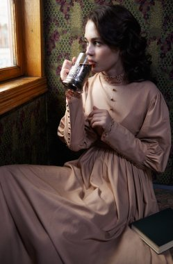 Young woman in beige vintage dress of early 20th century drinkin