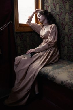 Young woman in beige vintage dress of early 20th century sleapin