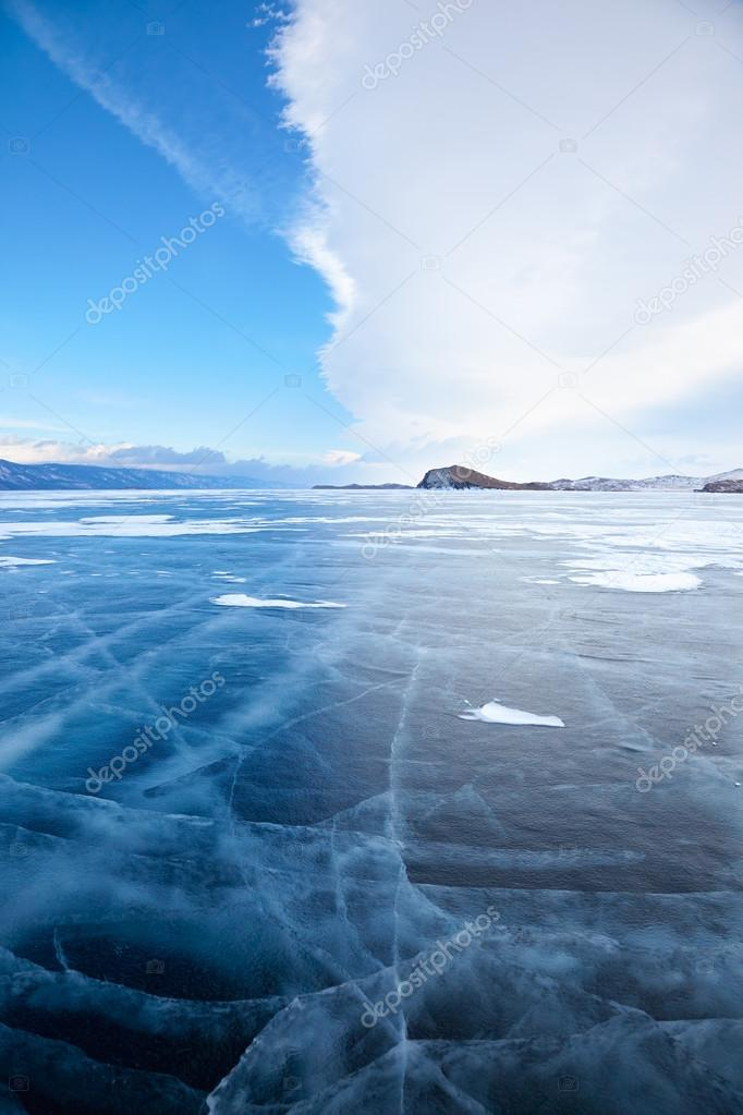 Winter ice landscape on lake Baikal with dramatic weather clouds