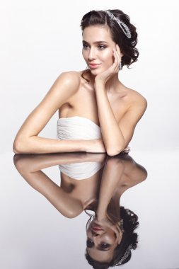 Portrait of young beautiful brunette woman sitting at mirror tab