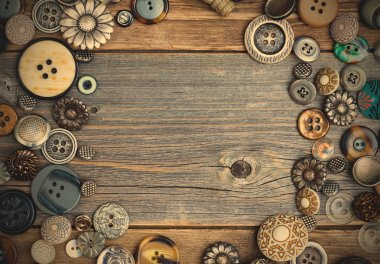 placer of vintage buttons with copy space on textured old boards