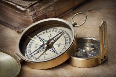 antique compasses on vintage paper background