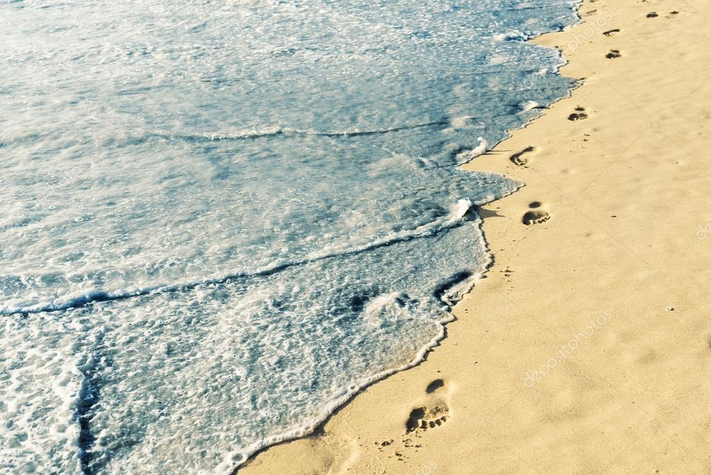 Footprints on sand with foam