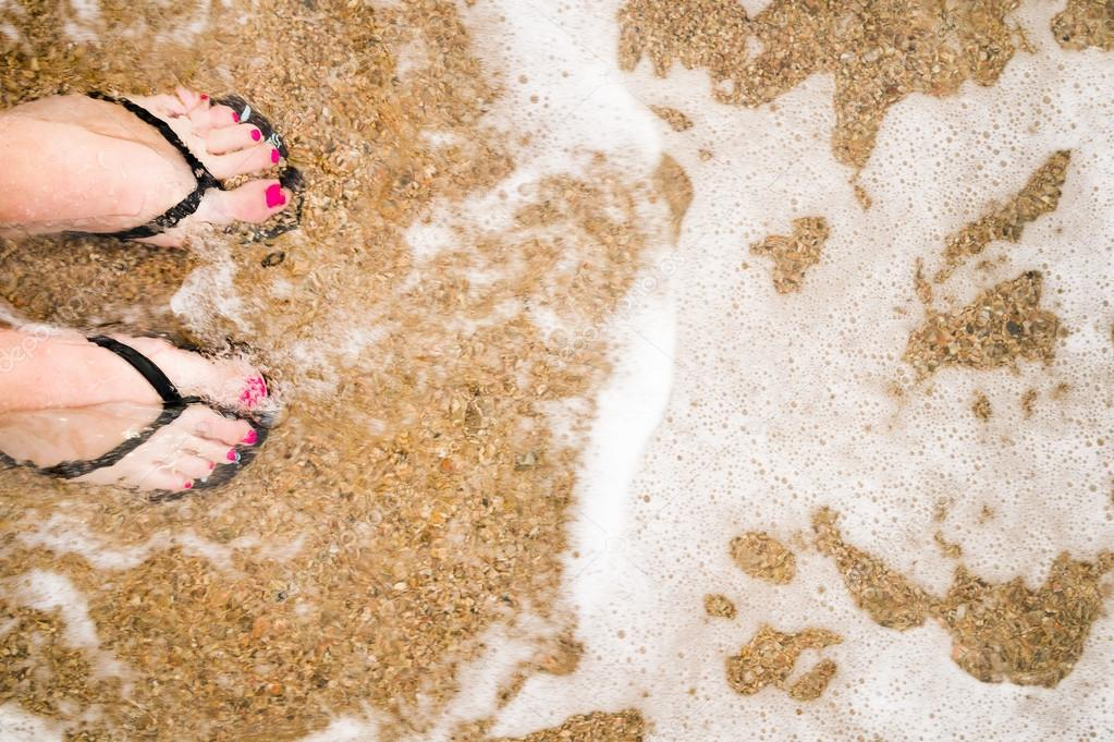 Female feet on beach