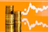 Fotografie zlaté peníze a kolísající graf