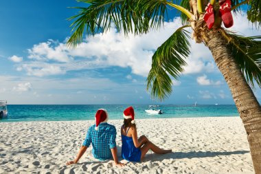 Couple in blue clothes on a tropical beach at Christmas stock vector