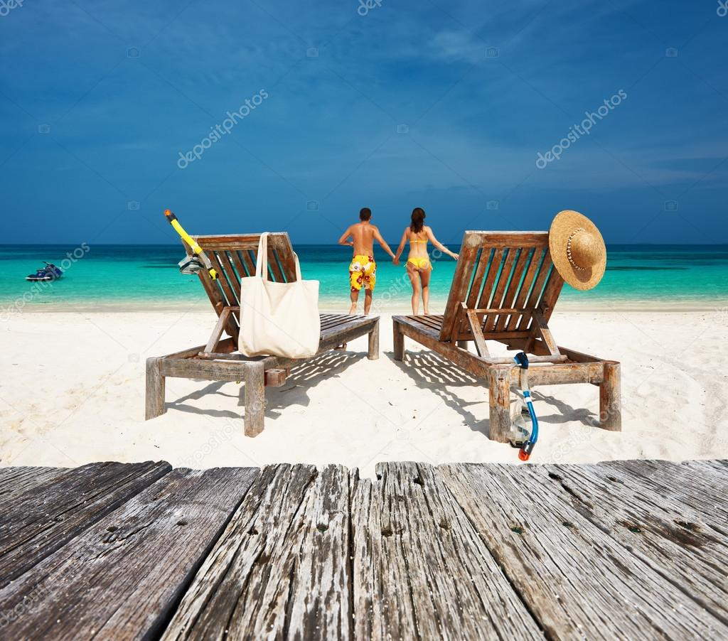 Couple in yellow relax on a beach