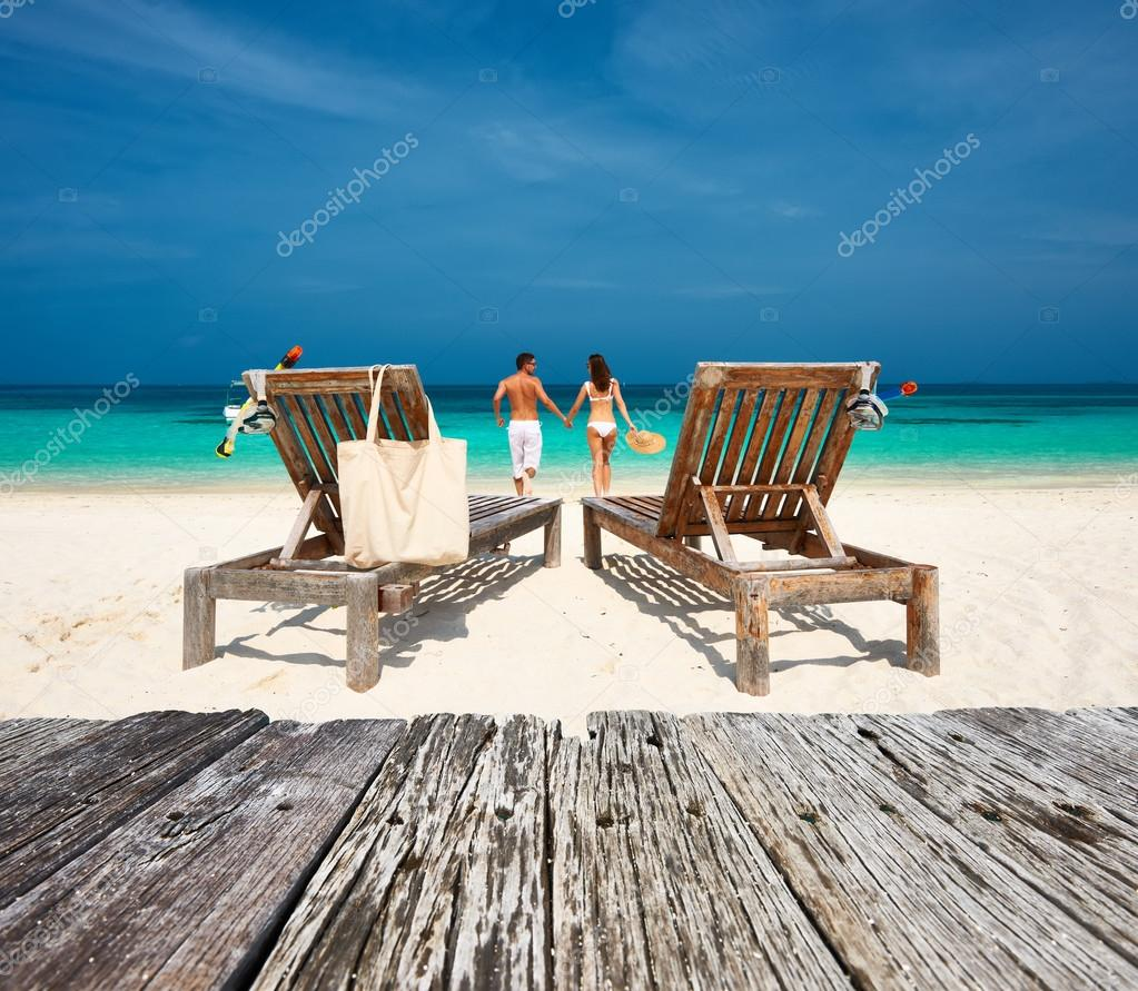 Couple in white relax on beach