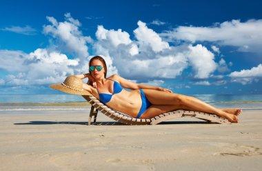 Woman in bikini lying on beach
