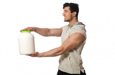 Muscular man with protein jars on white