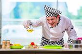Mužské kuchař připravuje jídlo v kuchyni