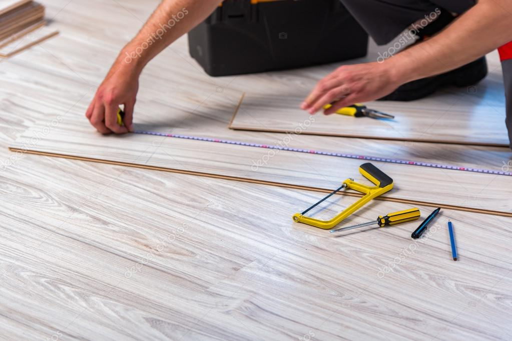 Man Laying Laminate Flooring In Construction Concept Stock Photo