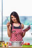 Ženské kuchař připravuje polévka v jasně osvětlené kuchyni