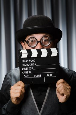 Funny man with movie board against curtain stock vector