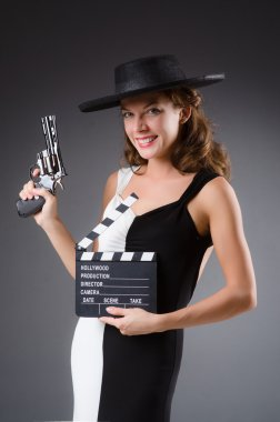 Young  Girl with gun and clapperboard on grey background stock vector