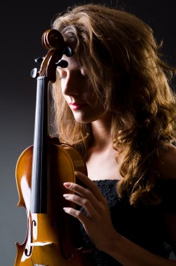 Female musical player against grey background