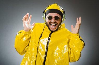 Man wearing yellow suit listening to headphones