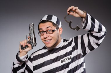 Young prisoner with cuffs and handgun against gray