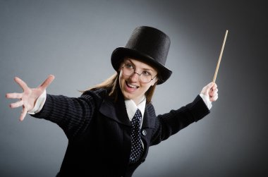 Harry Potter girl with magic stick against grey