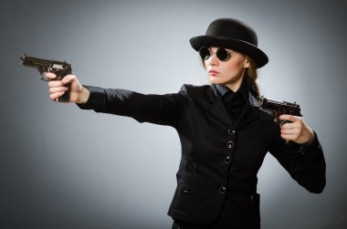 Female spy with weapon against gray